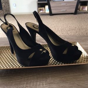 Black Guess heels with gold embellishment.
